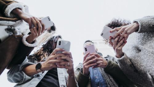 Mehrere junge Leute stehen zusammen und beschäftigen sich mit ihren Smartphones.