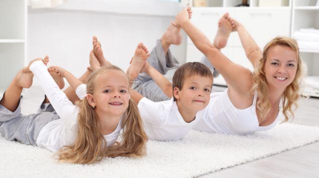 Mutter, Tochter und Sohn machen Gymnastik.