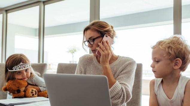 Das Bild zeigt eine junge Mutter mit ihren zwei Kindern, die vor einem Laptop sitzt und arbeitet.