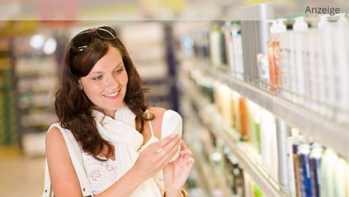Man sieht eine Frau, die in einer Drogerie ein Shampoo aus dem Regal nimmt.