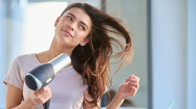 Eine junge Frau föhnt sich die Haare.