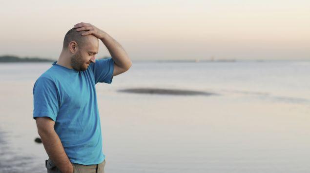 Ein glatzköpfiger Mann steht am Strand und fasst sich mit der linken Hand an den Kopf.