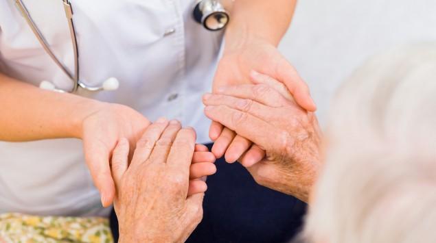 Eine Ärztin hält die Hände eines Seniors.