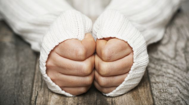 Eine Frau versteckt ihre Hände im Ärmel.
