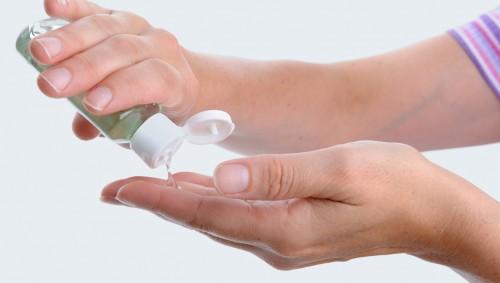 Eine Frau gibt Händedesinfektionsmittel auf ihre Hände.