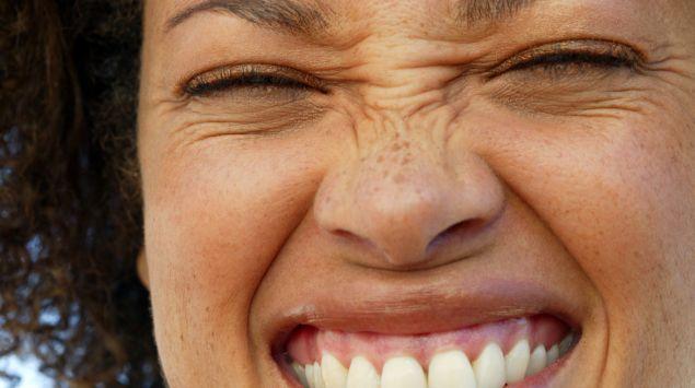 eine junge Frau rümpft ihre Nase und lächeln