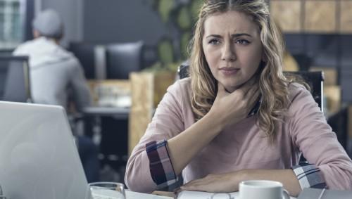 Eine Frau fasst sich im Büro an den schmerzenden Hals.