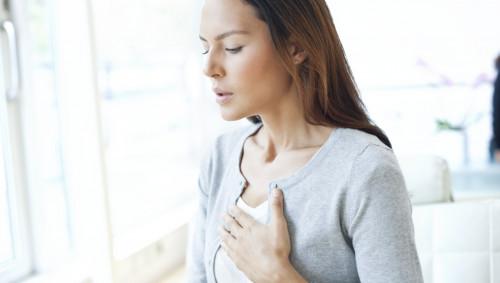 Eine junge Frau legt die linke Hand flach auf die Brustmitte.