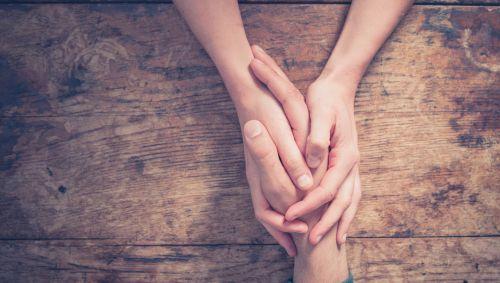 Jemand hält die Hand eines anderen.