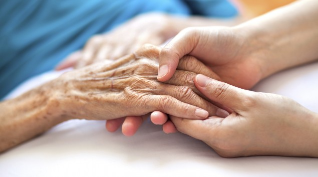 Eine junge Person hält einer älteren Person die Hand.