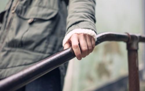 Eine Frau umfasst ein Treppengeländer mit der linken Hand.