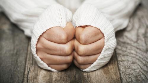 Eine Frau versteckt ihre Hände in den Ärmeln ihres Pullovers.