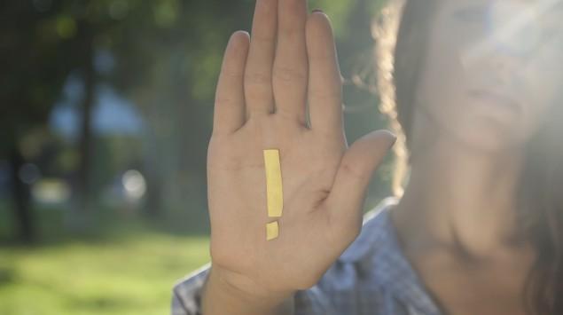 Eine Frau hält ihre Hand abwehrend nach vorn, darauf sieht man ein Ausrufezeichen.