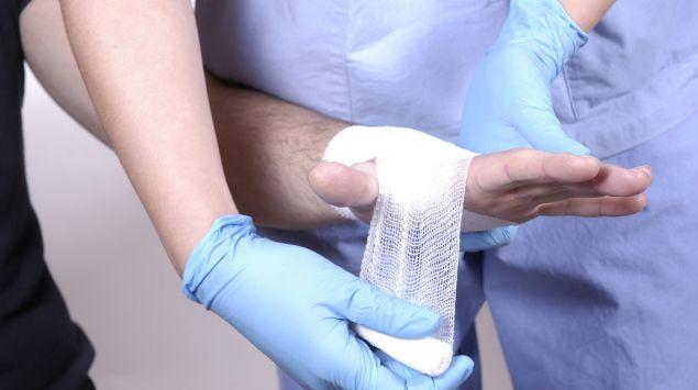 Einem Patienten wird die linke Hand bandagiert.