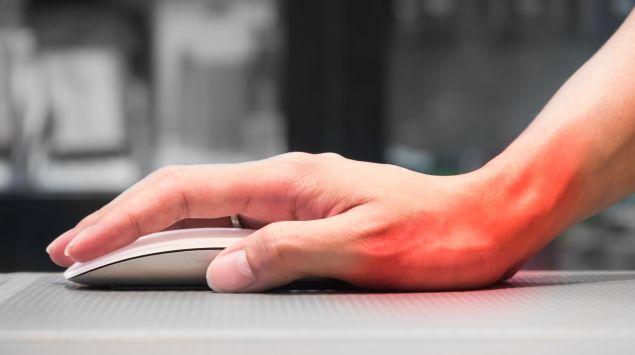 Das Bild zeigt eine schmerzende Hand auf einer Computermaus.
