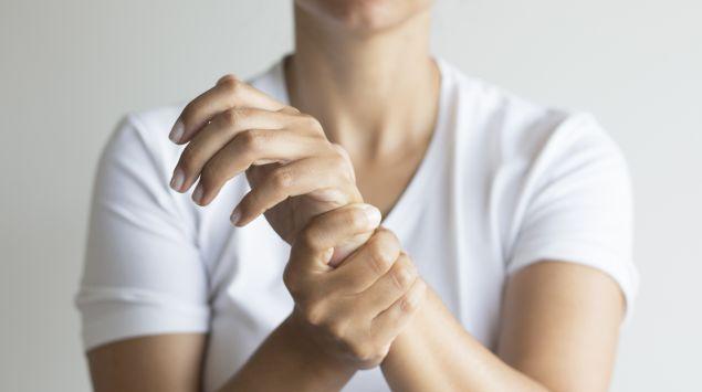 Frau Hält sich das Handgelenk, weil sie Schmerzen hat