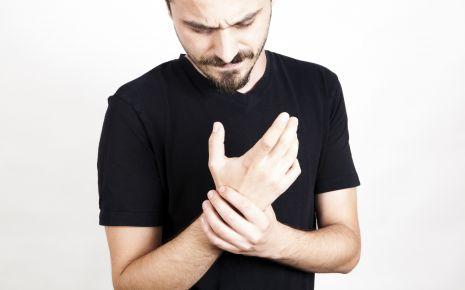 Ein Mann hält sich das schmerzende Handgelenk.