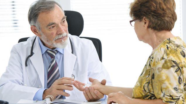 Ein Arzt hält die verletzte Hand einer älteren Frau.