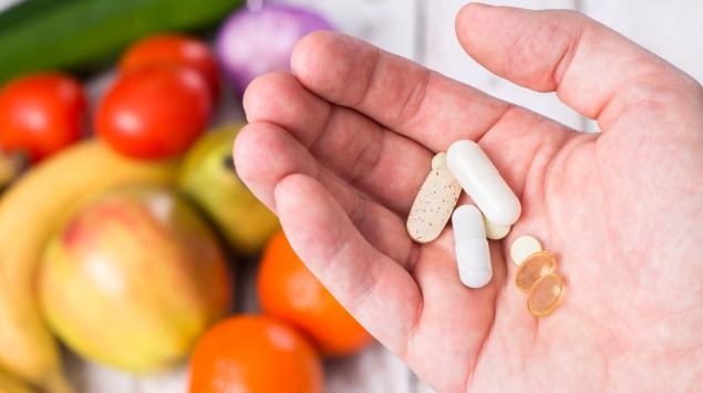 Jemand hät mehrere Tabletten in der Hand; im Hintergrund sind verschiedene Obst- und Gemüsesorten zu sehen.