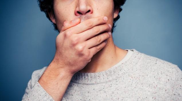 Ein Mann hält sich die Hand vor den Mund: Aphthen sind sehr schmerzhaft.