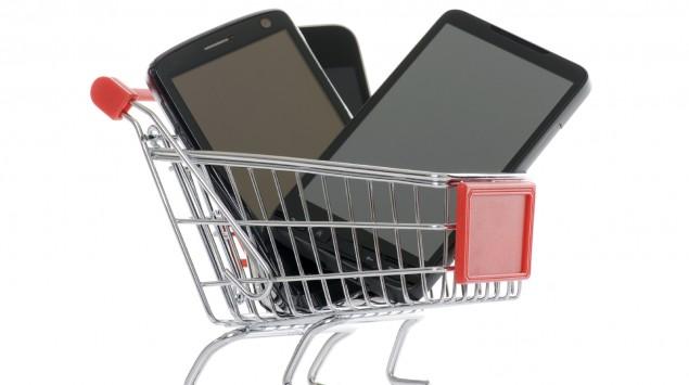 In einem Miniatur-Einkaufswagen liegen drei Handys.