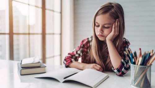 Ein Mädchen sitzt am Schreibtisch und starrt unmotiviert in sein Heft.