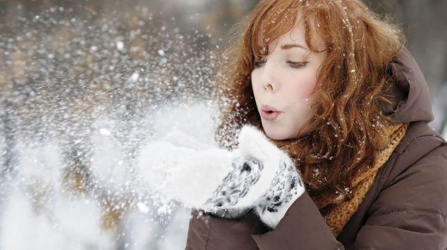 Das Bild zeigt eine Frau, die Schnee aus ihren Händen pustet.
