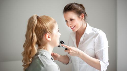 Eine Hautärztin untersucht ihre Patientin mit einem Dermatoskop.