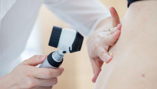 Ein Hautarzt untersucht einen Patienten.
