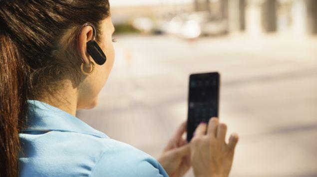 Eine Frau nutzt zum mobilen Telefonieren ein Headset.