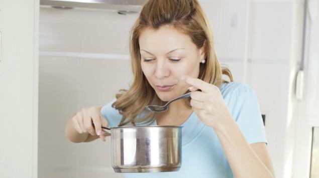 Eine Frau isst aus einem Topf.