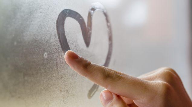 Jemand malt mit dem Finger ein Herz auf eine beschlagene Fensterscheibe.