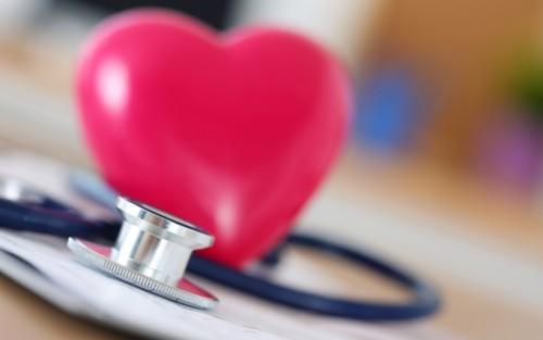 Man sieht ein Herz und ein Stethoskop.