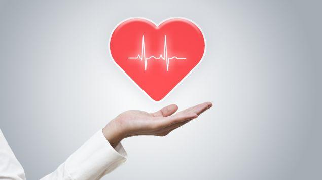 Das Bild zeigt das Herzsymbol, das über der Hand einer Ärztin schwebt.