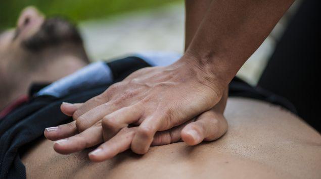Jemand führt bei einem Mann eine Herzdruckmassage durch.