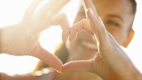 Eine Frau formt mit den Fingern ein Herz.