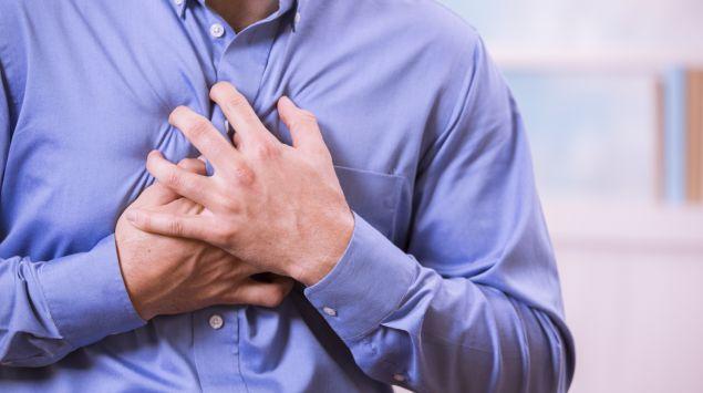 Ein Mann greift sich an die Brust.
