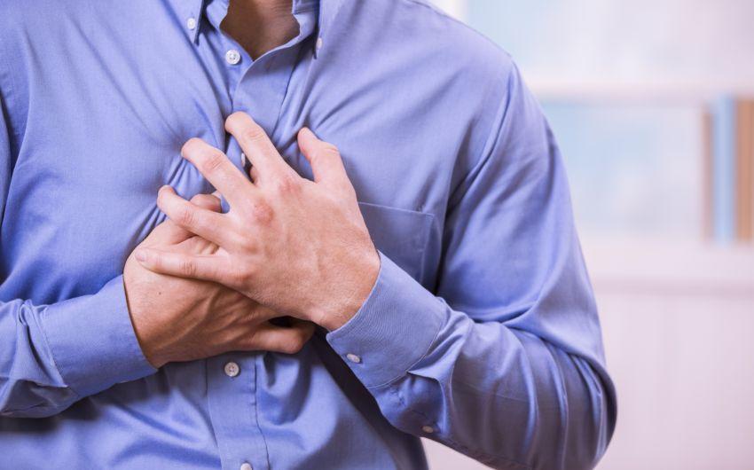 Ein Mann fasst sich an die Brust.