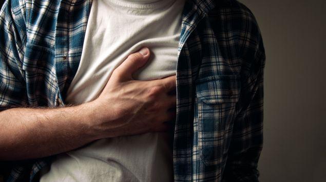 Mann hält sich die Brust.