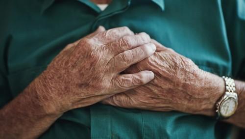 Ein älterer Mann fast sich mit beiden Händen an die Brust.