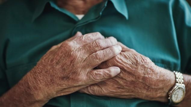 Älterer Mann fasst sich an die Brust.