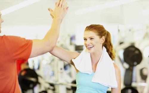 Eine lachende Frau im Fitnessstudio schlägt ihre erhobene rechte Hand gegen die eines Mannes.