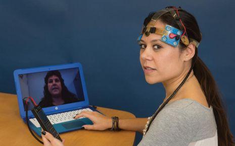 Ein Mitglied des Forscherteams testet die Funktion der Elektroden auf dem Kopf.
