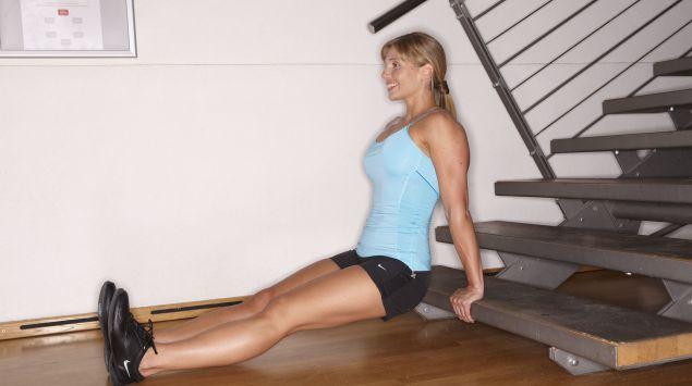 Man sieht eine Frau, die eine Übung an einer Treppenstufe macht.