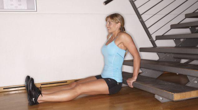 Man sieht eine Frau, die eine Kraftübung an einer Treppenstufe macht.