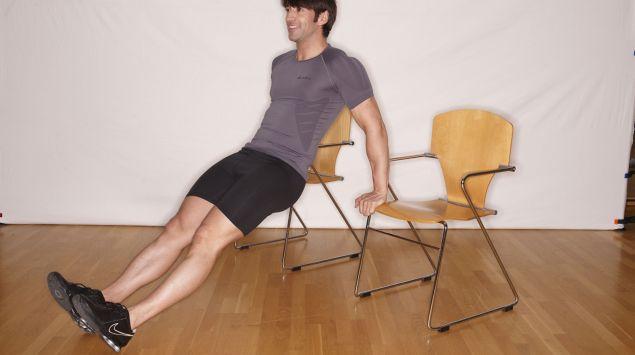 Man sieht einen Mann, der Übungen an zwei Stühlen macht.