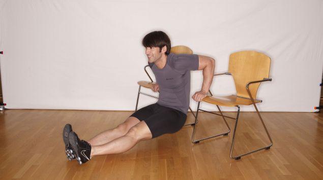 Man sieht einen Mann, der Übungen an einem Stuhl macht.