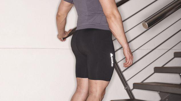 Man sieht einen Mann, der eine Übung auf einer Treppe macht.