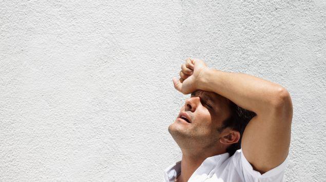 Ein Mann hält sich draußen vor Hitze und Erschöpfung den Arm vor die Stirn.