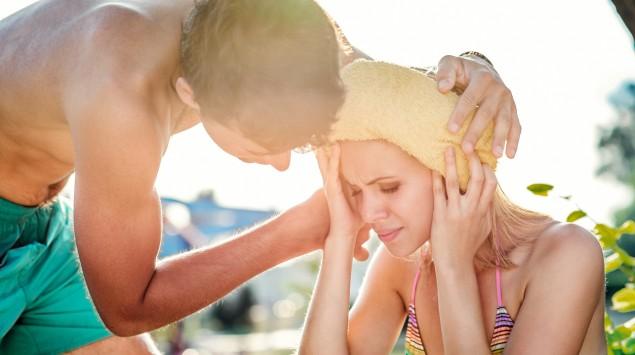 Ein Mann in badehosen legt einer Frau im Bikini ein feuchtes Handtuch auf den Kopf.